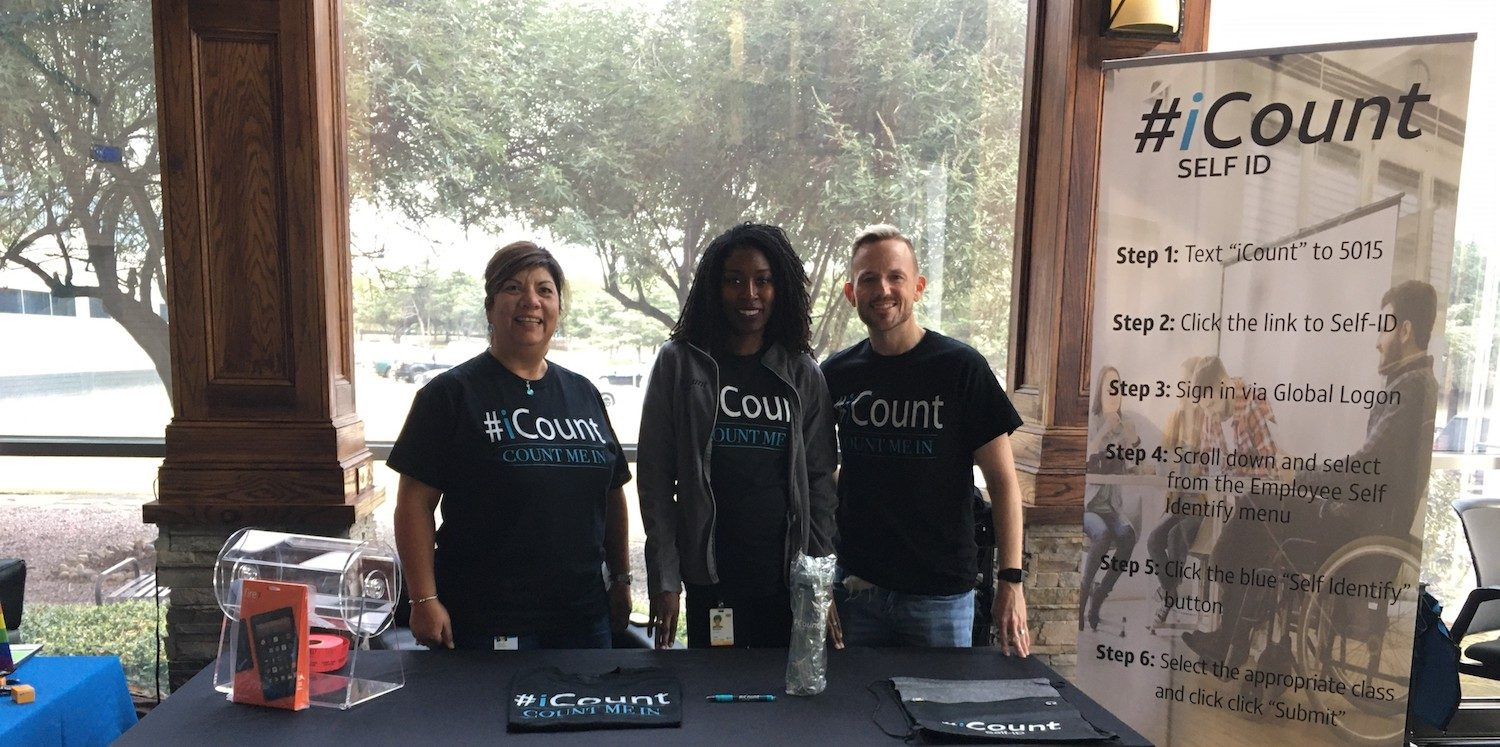 3 members of icount team standing at outdoor booth